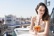 Sunset Lookers modelo con en mesa con cocktail